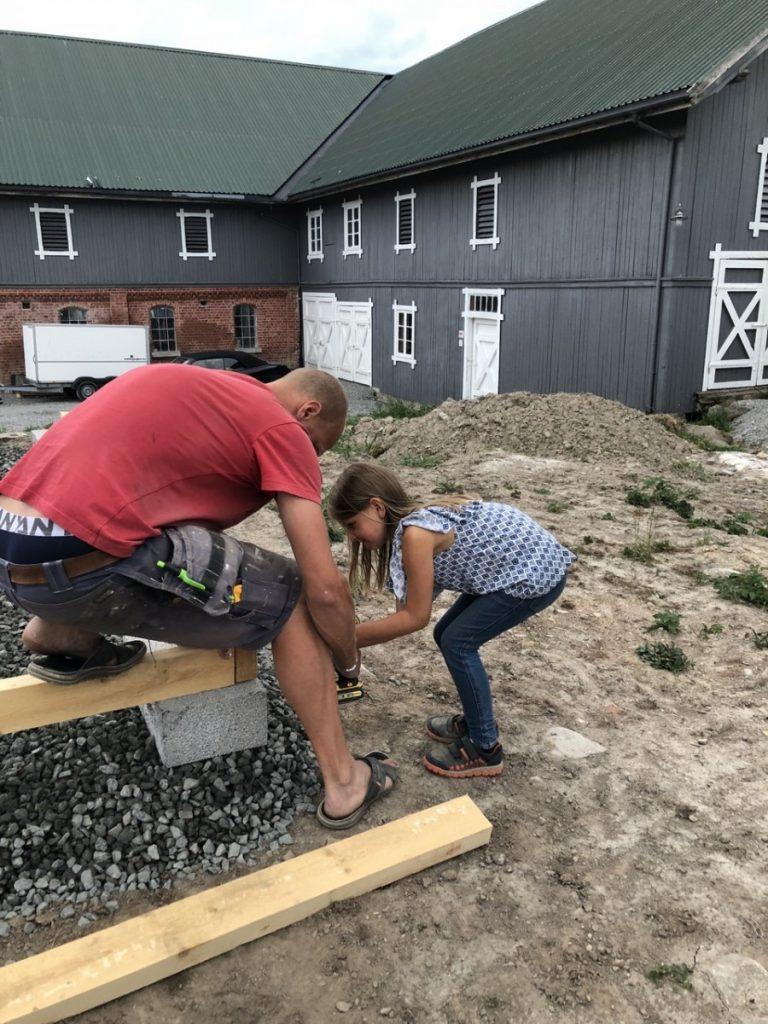 Anna hjelper pappa å bygge lekestue på Skjeggenes